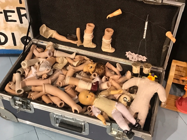 A trunk filled with doll parts.